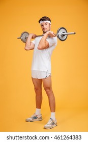 Playful young sportsman holding barbell and making funny face over yellow background