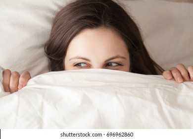 Playful young woman hiding face under blanket while lying in cozy bed on white pillow, pretty curious girl feeling shy peeking from duvet, covering with white sheet, head shot close up, top view