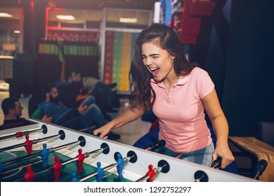 Playful young woman play table soccer in room. She scream. Model rejoice. Young men behind sit and play games.