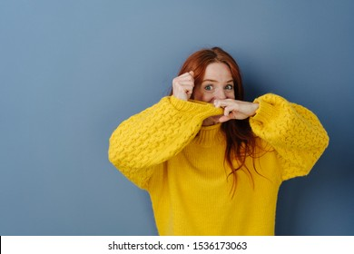 Playful young woman pulling at the sleeve of a bright yellow sweater and peering over the top at camera with wide eyed anticipation over a blue studio background with copy space