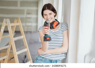 Playful young woman taking aim at the camera with an electric drill as she does DIY renovations in her new home