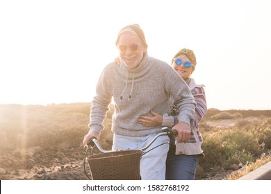 Playful and youthful senior caucasian peope couple enjoy a ride with bike together laughing and smiling -    concept of happiness and joyful intoegther forever life with love