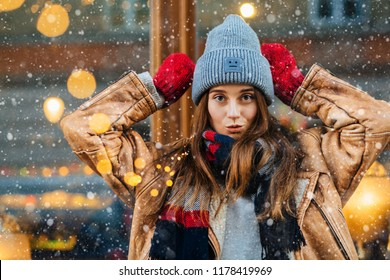 Playfull smiling woman in warm winter clothing standing with hands in red gloves like deers on the street of european city with light of garland on background. Winter holidays concept. Snowfall.