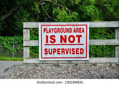 Playground area is not supervised sign posted in a wooden fence