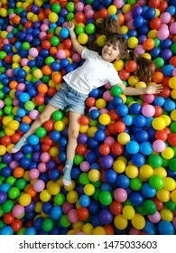 Playground with ball pit indoor. Joyful kid having fun at indoor play center. Children playing with colorful balls in playground ball pool. Holiday or birthday.