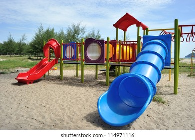 Playground with blue tunnel slider on the beach