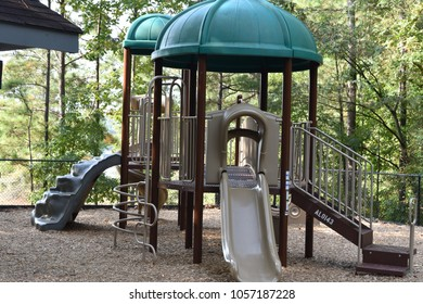 Playground Equipment with Green Trees in the Background that is Sitting Empty Waiting for Children