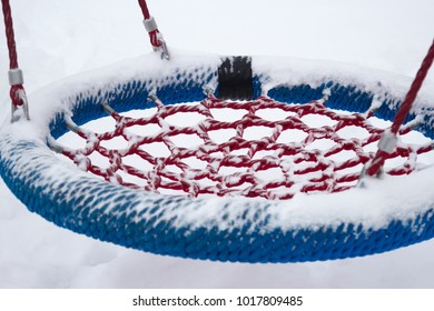 The playground in snow. Swing clope up