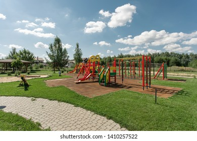 Playground in summer. Baby swings and benches on a playground viewed on a sunny day
