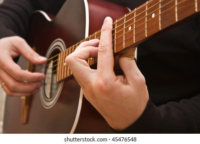 Playing acoustic guitar, barre chord