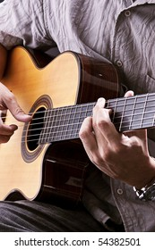 Playing acoustic guitar. Studio photography.