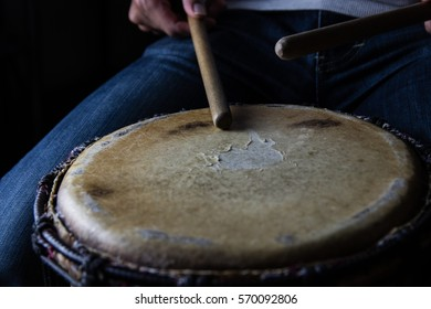 Playing African Drums in Low Key Single Light by Musician in Music Studio, West Africa.
