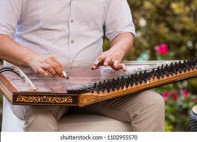 playing an Arabic stringed musical instrument