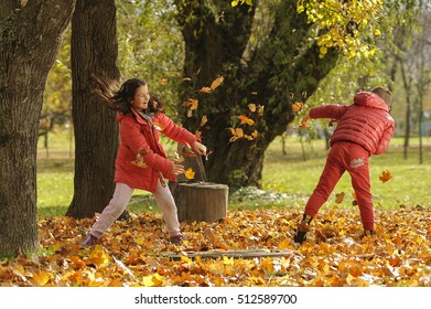 Playing in the autumn environment. Kids outdoors, the children in the park, playing in the season of autumn colors.
