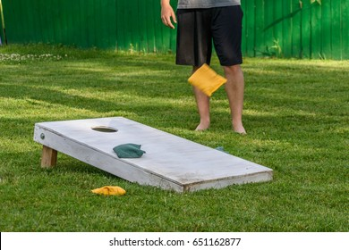 Playing bags or cornhole game in backyard on sunny day