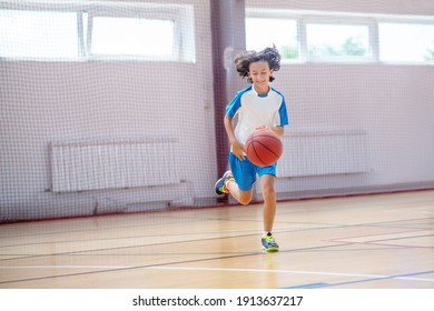 Playing basketball. Boy in sportswear running after the ball in a gym