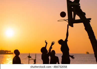 Playing basketball at the shore at sunset
