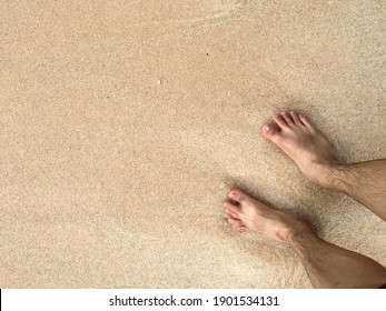 Playing with the beach sand on barefoot