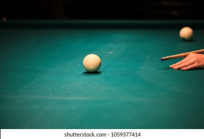 Playing billiard. Billiards balls and cue on green billiards table. Russian pyramid.