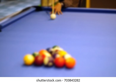 Playing billiard - blurry image of hand cueing the ball