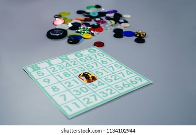 playing bingo with a bingo card and fake jewels and buttons as bingo markers