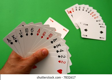 """playing bridge - one hand (A,K,J,10,6 spades, 2 heart, A,Q,10 diamonds, A,K,4,2 clubs),  on table other """"bridge hand""""  and lead Ace heart,  background green, selective focus"""