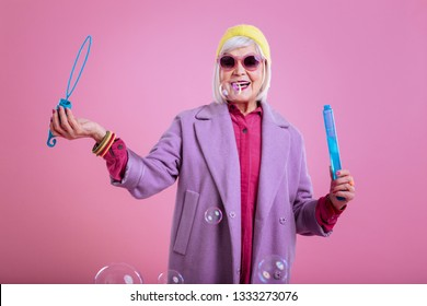 Playing with bubbles. Lovely elderly lady wearing pink and purple clothes playing with soap bubbles