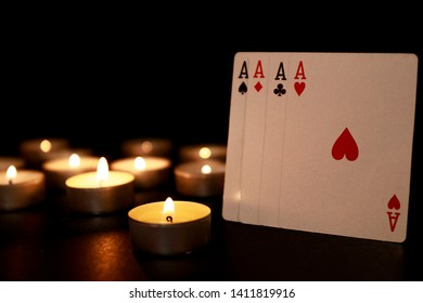Playing card ace on dark background with candle light. Four aces. Poker of aces.