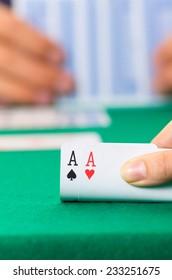 Playing cards closeup of hands lifting pair of aces cuarenta traditional Ecuadorian game selective focus