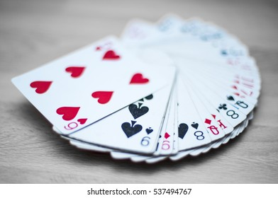 Playing cards deck isolated on a gray wooden background - red, black, and white colors