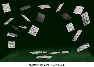 playing cards fall on a green table