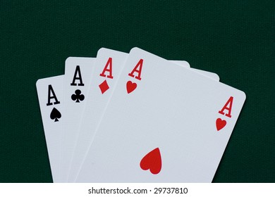 Playing cards - four aces on green background.