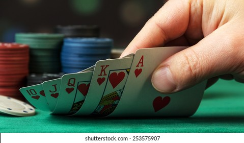 Playing Cards in hand on green background