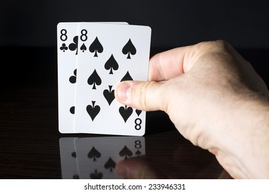 Playing cards, a pair held in a hand on a dark background.