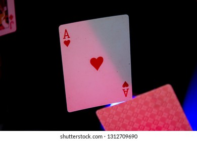 Playing cards with pink, blue light on black background. Cards ace fall down.