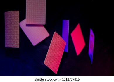 Playing cards with pink, blue light on black background. Cards fall down.