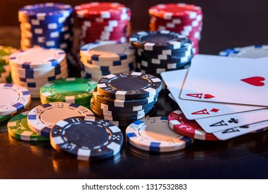 Playing cards with poker chips at black background