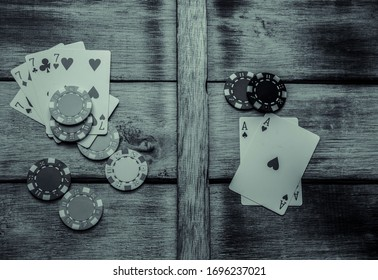 Playing cards and poker chips on wooden table black and white