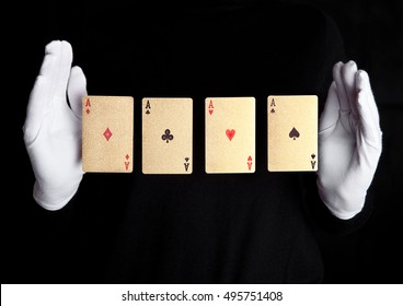 Playing cards trick with ace hands with gloves on black background