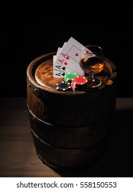 Playing cards and wine glass of cognac on barrel.