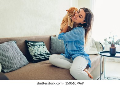Playing with cat at home. Young woman sitting on couch and hugging pet.