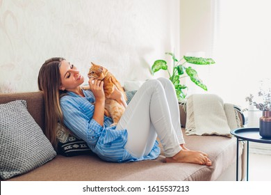 Playing with cat at home. Young woman sitting and relaxing on couch in living room and hugging, playing with pet.