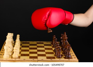 Playing chess in boxing gloves isolated on black