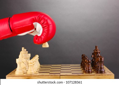 Playing chess in boxing gloves on grey background