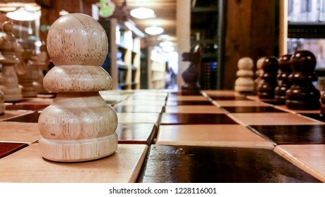 Playing chess with large wooden pieces in a library at close up and low angle