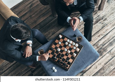 Playing chess. Top view of young thoughtful men in full suits playing chess while sitting indoors