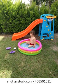Playing child in garden with toy pool