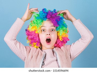 Playing the clown. Adorable small clown with opened mouth. Cute little girl wearing colorful clown wig hair. She is a clown.