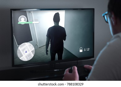 Playing console games or video game addiction concept. Person looking at TV screen very close and holding controller or gamepad. Addicted gamer. Nerdy young man, geek or nerd at home late at night.