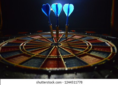 Playing darts and hitting bull's eye. Sport entertainment darts.